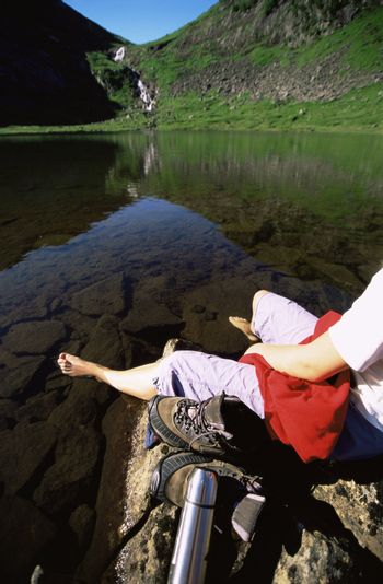Woman's legs outdoors at campsite on large rocks