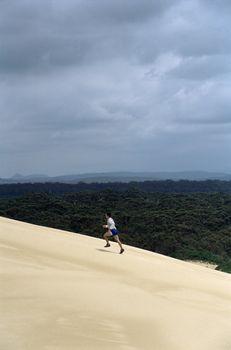 Man outdoors on sandy hill running