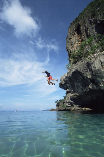 Couple outdoors jumping off cliff into ocean