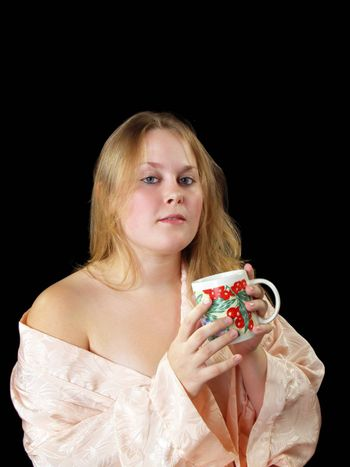 Young woman in peach robe with coffee or tea cup