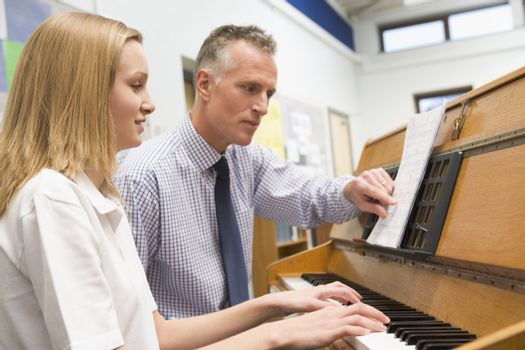 Female student learning piano with teacher in classroom