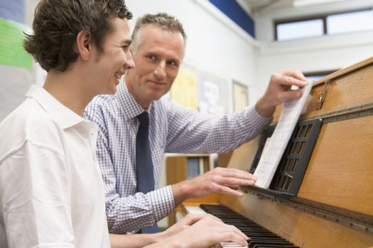 Male student learning piano with teacher in classroom