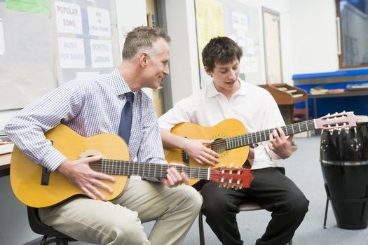 Male student receiving guitar lesson from teacher in classroom