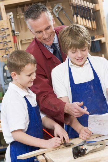 Male students reviewing woodworking plans with teacher