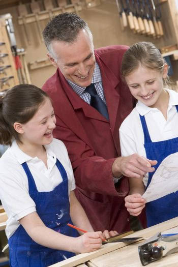 Female students reviewing woodworking plans with teacher