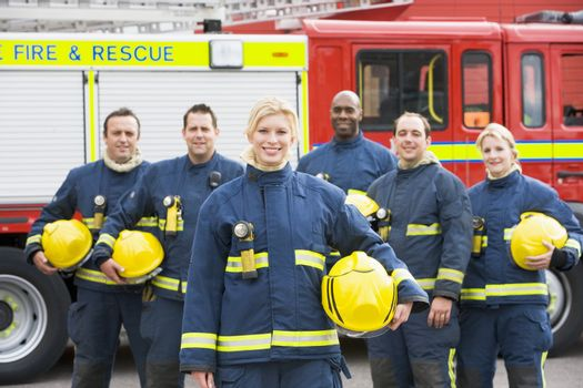Six firefighters standing by fire engine