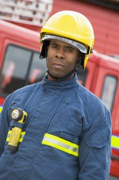 Fireman standing by fire engine wearing helmet