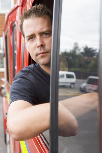 Fireman sitting in fire engine with head out window