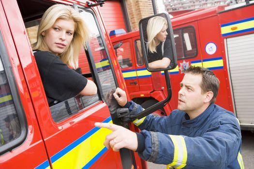 Firewoman sitting in fire engine talking to fireman standing outside