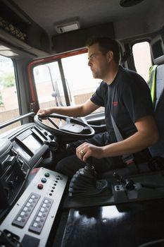 Fireman in fire engine holding steering wheel
