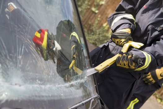 Firefighter cutting out a windshield after an accident