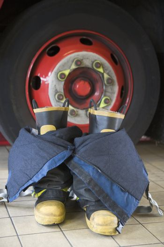Firefighting uniform on floor by fire engine