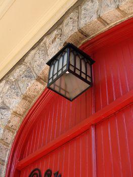 black lantern hanging by red doors