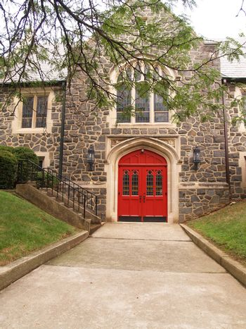 concrete sidewalk leading to two red doors for an old stone building