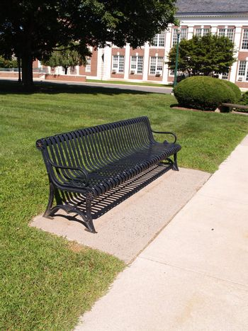 one black empty wrought iron bench by a sidewalk