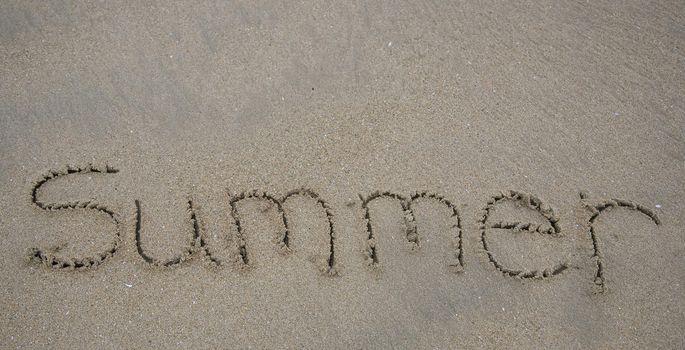 The word Summer written in beach sand