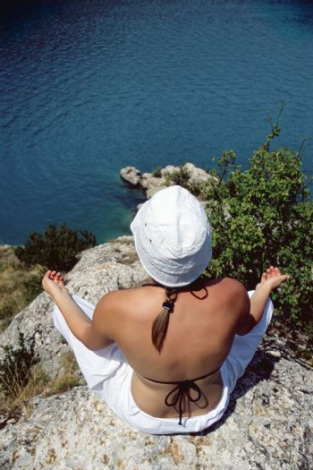Woman outdoors doing yoga on cliff