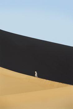 Man outdoors walking in the desert (far away)