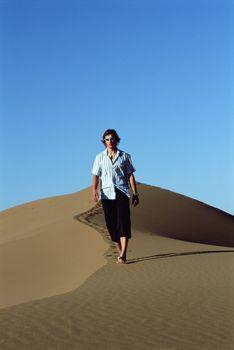 Man outdoors walking in the desert