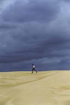 Man outdoors running in the desert (far away)