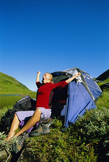 Woman outdoors at campsite by lake yawning and stretching