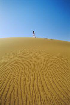 Woman outdoors walking in the desert (far away)