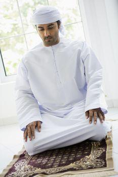 Man indoors praying on mat (high key)