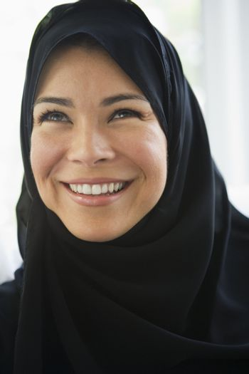Woman standing indoors smiling (high key)