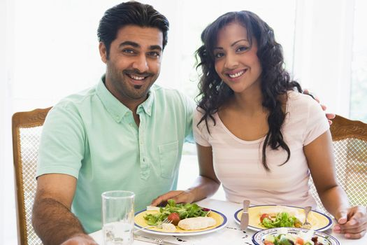 Couple sitting at dinner table smiling (high key)