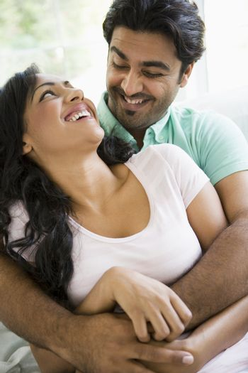Couple in living room embracing and smiling (high key)