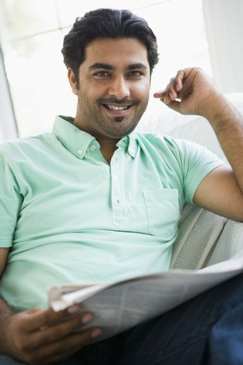 Man in living room with newspaper smiling (high key/selective focus)