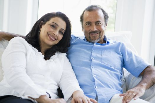 Couple sitting in living room smiling (high key)
