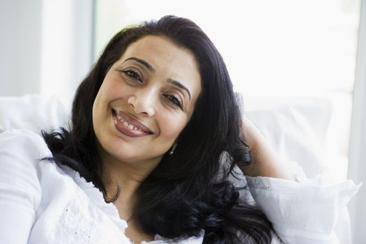 Woman sitting in living room smiling (high key)