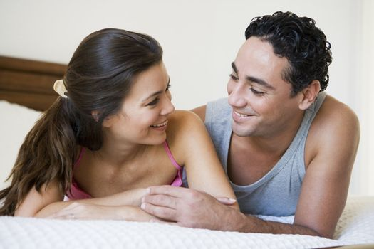 Couple relaxing on bed in bedroom smiling (selective focus)