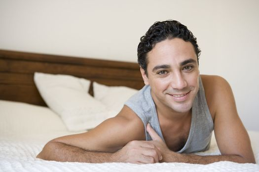 Man relaxing on bed in bedroom smiling (selective focus)