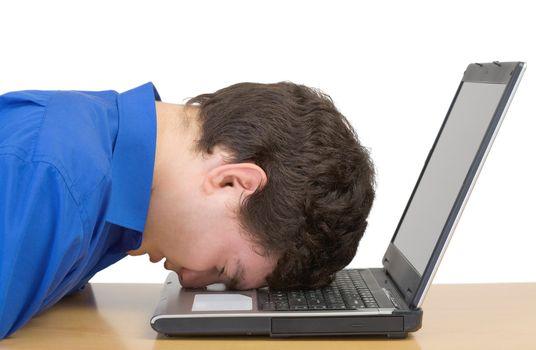Man in despair buried head in computer keyboard