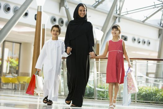 Woman and two young children walking in mall smiling (selective focus)