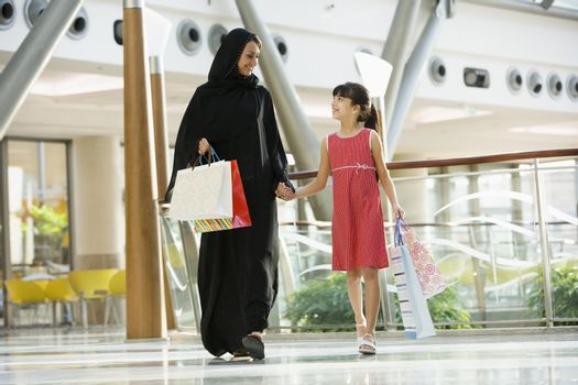Woman and young girl walking in mall smiling (selective focus)