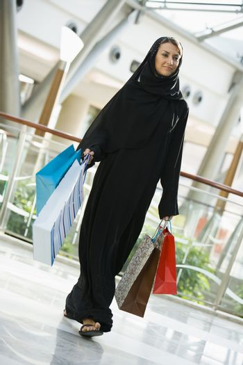 Woman walking in mall smiling (selective focus)