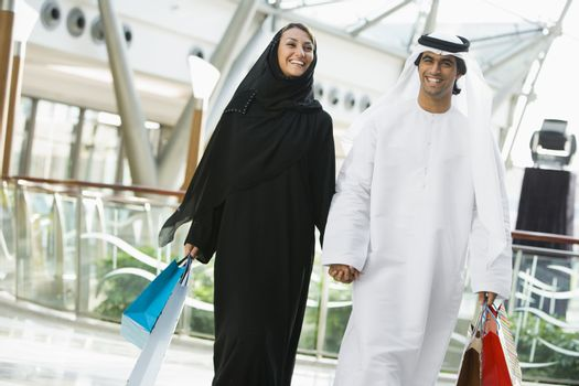 Couple walking in mall holding hands and smiling (selective focus)