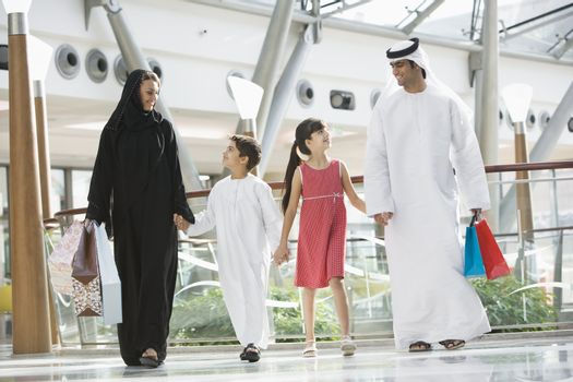 Family walking in mall holding hands and smiling (selective focus)