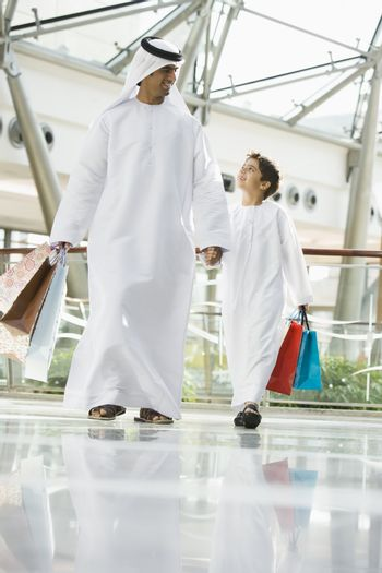 Man and young boy walking in mall holding hands and smiling (selective focus)