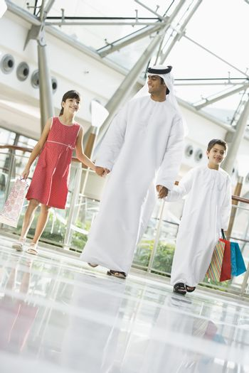 Man and two young children walking in mall holding hands and smiling (selective focus)