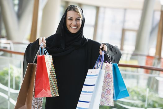 Woman standing in mall smiling (selective focus)