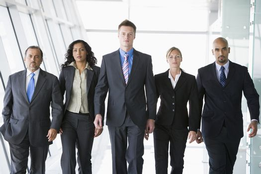 Group of co-workers walking in office space (high key)