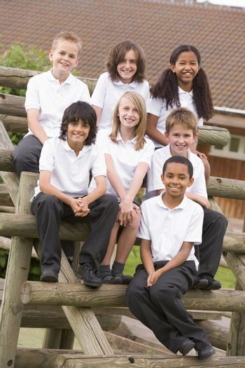 Seven students sitting on wooden structure outdoors