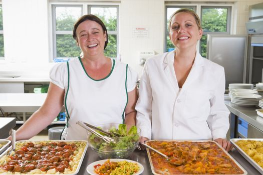 Two lunch ladies standing behind full lunch service station