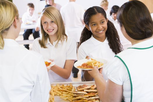 Students in cafeteria line being served by lunch ladies