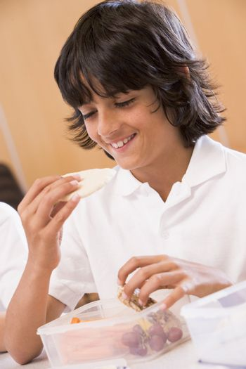 Student in cafeteria eating lunch (selective focus)