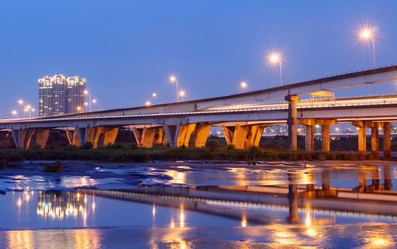 Color city scenic with modern bridge and light over river.